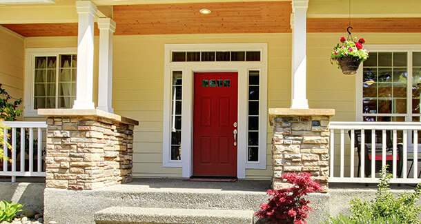 A modern, red steel entry door on home with two replacement windows.
