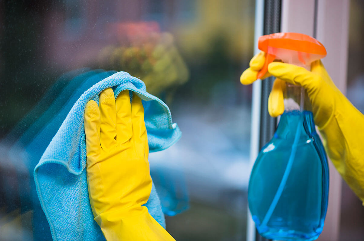 A person wearing yellow latex gloves, cleaning a window with a cloth and cleaner.