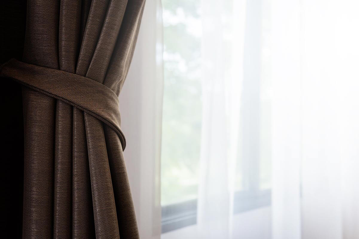 A brown curtain with a window in the background.