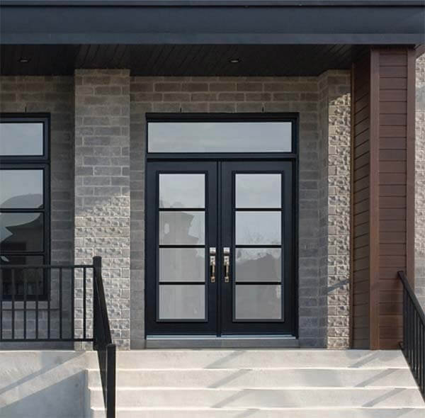 Modern, black double doors with rectangular transom freshly installed in a brick house.