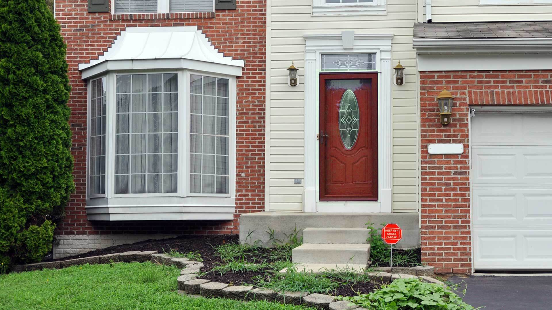This Detached House In Red Brick Has A Large Bay Window With Colonial Style Grilles