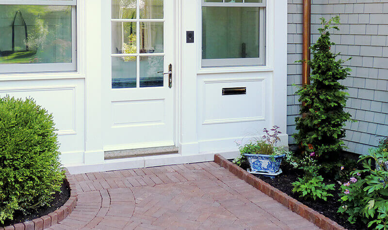 A white residential door with custom granite sill