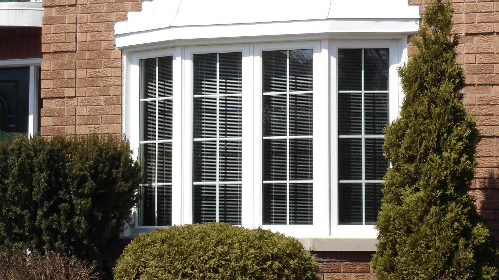 The front of a house with a window with grilles.