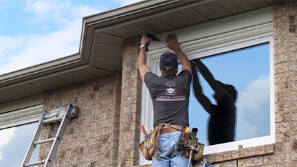 A Northern Comfort Installer Installing a second story window.