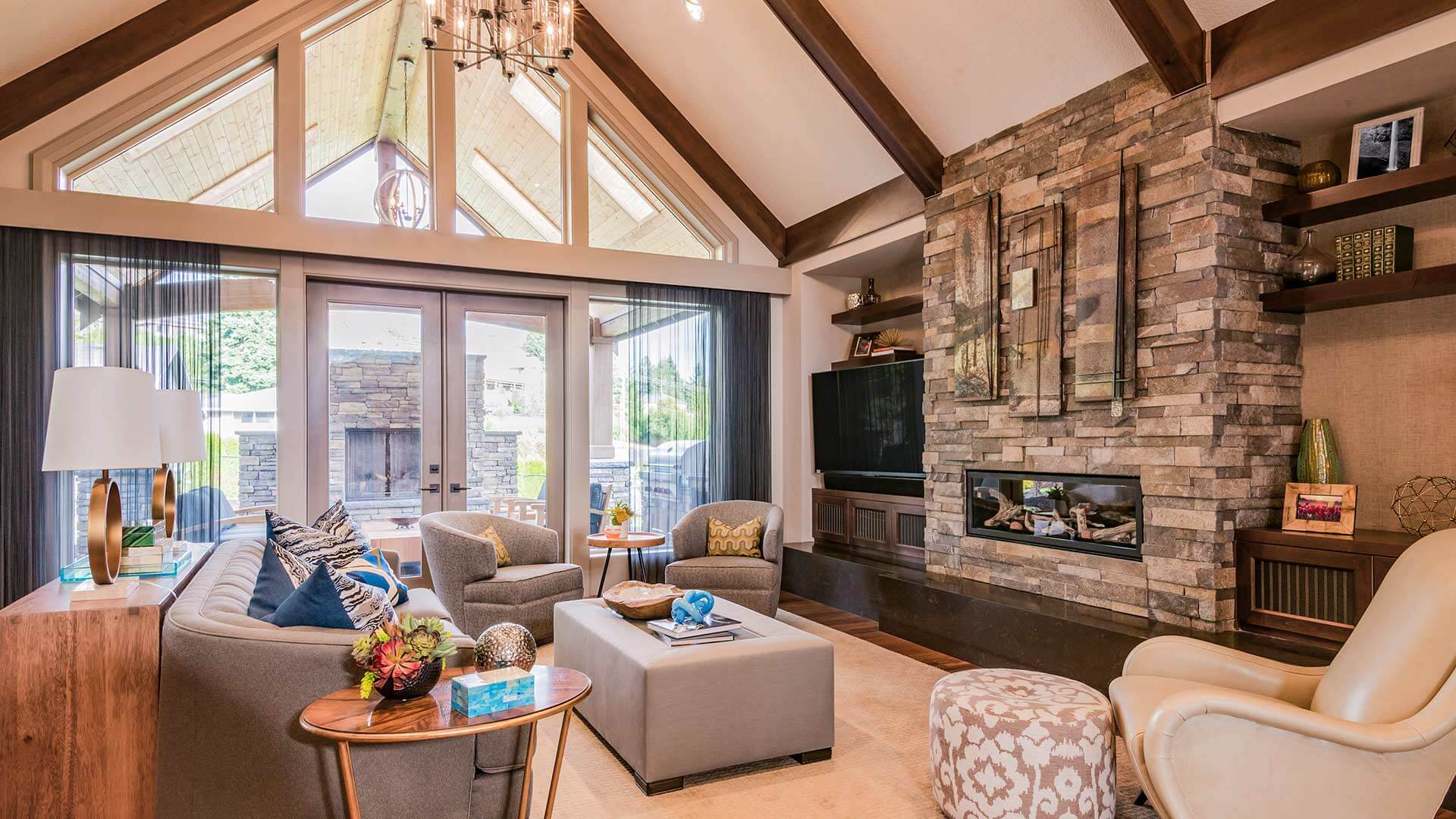 Modern living room featuring a slanted cathedral ceiling supported by solid wood rafters, and a fieldstone-veneer fireplace.