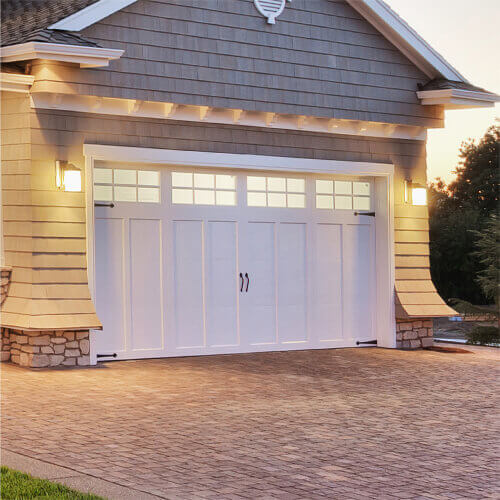 White garage doors in the front of the modern home