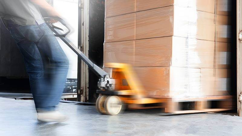 A photo of a pallet truck pulling a pallet filled with boxes