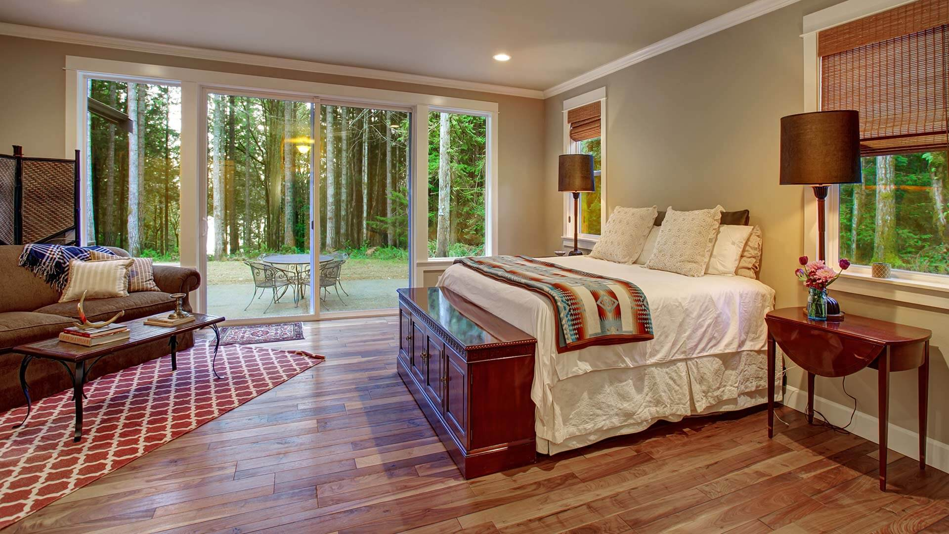 Patio doors with sidelites installed in a bedroom with rustic wood flooring.