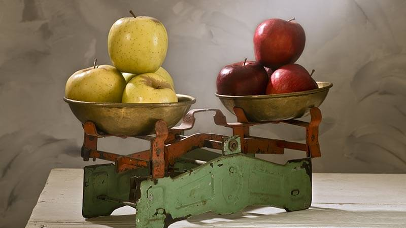 A photo of a balanced scale holding apples