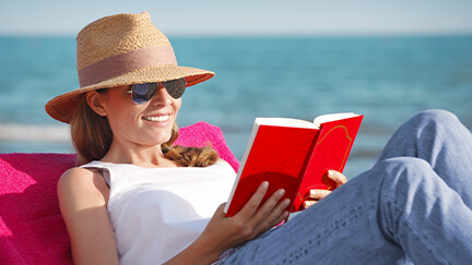 A woman reading a book on the beach knowing that she won't have to make a payment on her windows and doors for three months.