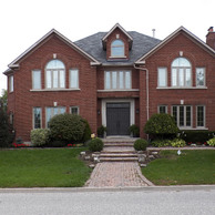 symmetrical brick home with shaped and casement windows