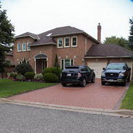 two car garage home with three small windows and arched doorway