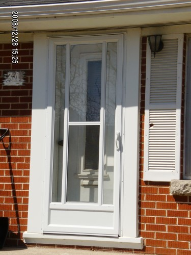 white storm door on brick house