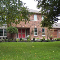 brick house with two car garage doors and shaped window