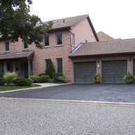 brick home with three garage doors