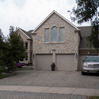 tan stone house with three car grage