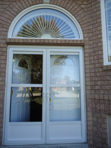 white storm doors with arch window overhead
