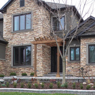 stone home with pergola over front door close up view
