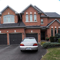 brick home with three brown garage doors